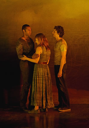The black man in tight multi-patterend t-shert and jeans is facing the white woman in a long, checkered dress, her sleeveless arms embracing his arms, as the white man in pale t-shirt and dark pants looks at the black man